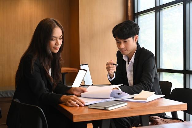 Groupe de responsable du service des ressources humaines lisant ensemble le document de cv d'un candidat employé.