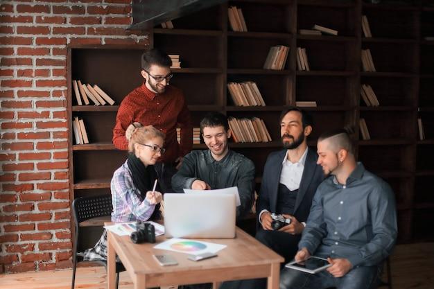 Groupe réussi de concepteurs discutant d'un nouveau projet de publicité