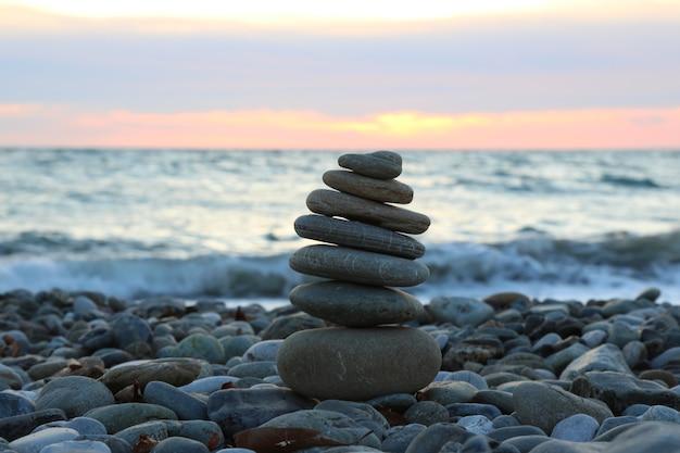 Un groupe de rochers sur la plage dans la nature. une pyramide de pierres sur une plage de galets, en arrière-plan un arrière-plan flou de la mer et du ciel au coucher du soleil, le concept d'équilibre et d'harmonie