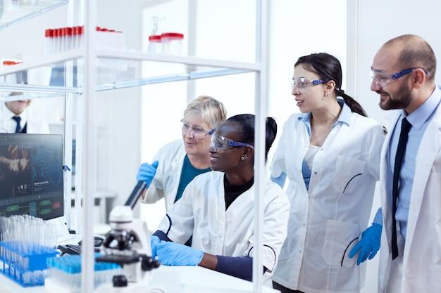 Groupe de scientifiques en pharmacie multiethnique en blouses de laboratoire travaillant ensemble dans un établissement moderne. chercheur en soins de santé noir dans un laboratoire de biochimie portant un équipement stérile.