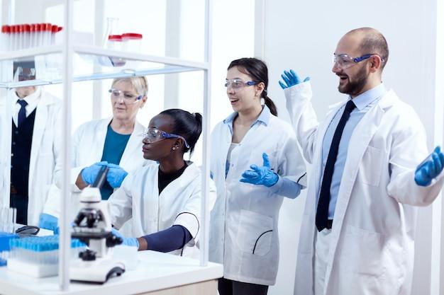 Groupe de scientifiques de race diverse travaillant pour trouver un remède contre le virus pendant la pandémie. chercheur en soins de santé noir dans un laboratoire de biochimie portant un équipement stérile.