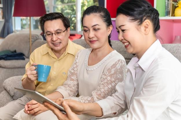 Groupe de senior asiatique à la retraite à la recherche de tablette en maison de retraite.