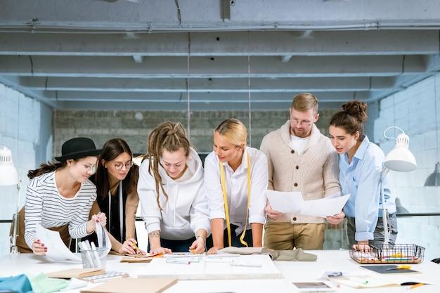 Groupe de six jeunes créateurs se penchant sur un bureau tout en discutant de trucs pour une nouvelle collection de mode en studio