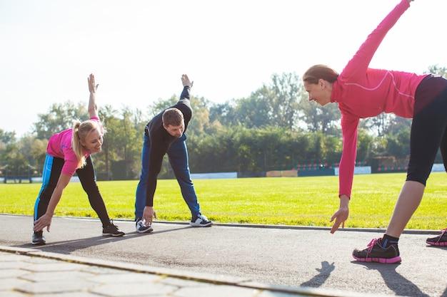 Un groupe de sportifs fait les exercices sur le stade