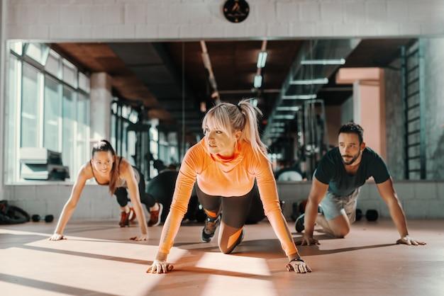 Groupe de sportifs avec de saines habitudes de vie faisant des exercices de force sur le sol de la salle de gym dans le miroir de fond.