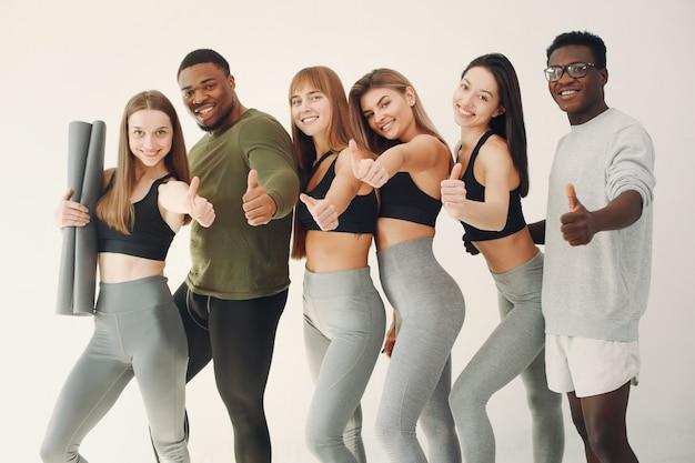 Groupe de sports debout sur un mur blanc