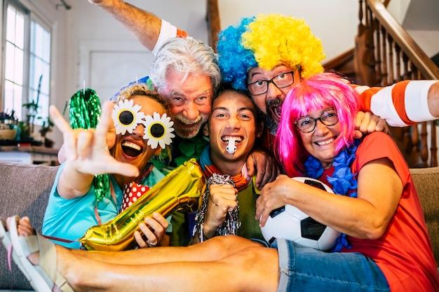 Un groupe de supporters de football fous et heureux à la maison profite du match et s'amuse tous ensemble