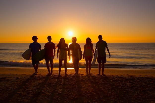 Groupe de surfeurs garçons et filles marchant sur la plage