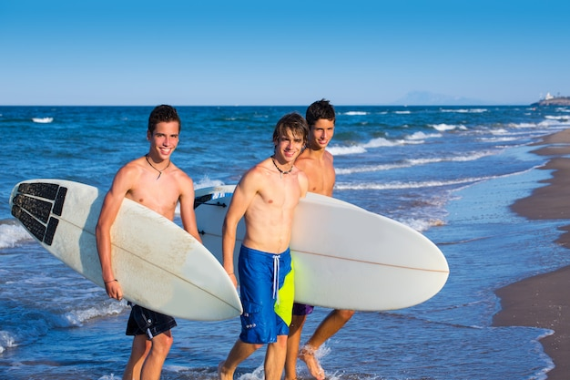 Groupe de surfeurs garçons sortant de la plage