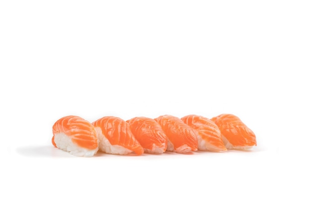 Un groupe de sushi saumon dans la rangée. c'est ce que la cuisine japonaise traditionnelle mange entre du saumon frais cru et du riz.