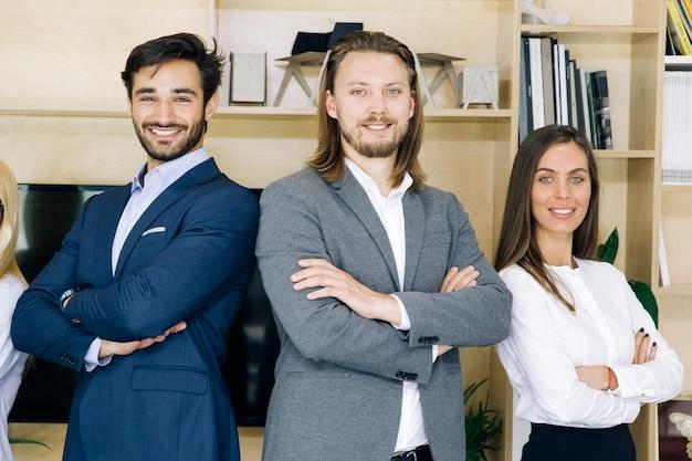 Groupe de sympathiques hommes d'affaires en costume debout au bureau