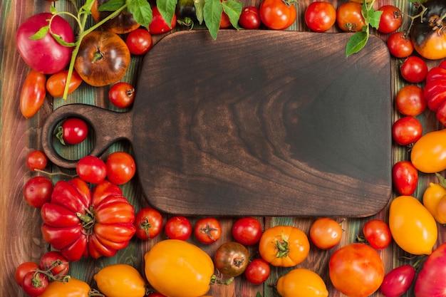 Groupe de tomates fraîches. belles tomates mûres de différentes variétés et planche à découper en bois. copier l'espace pour insérer du texte