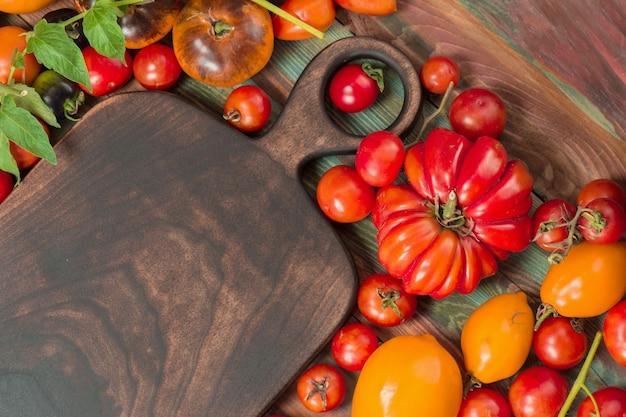 Groupe de tomates fraîches et planche à découper en bois