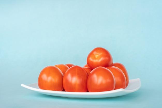 Groupe de tomates fraîches sur plaque blanche sur fond bleu. gros plan stock photo