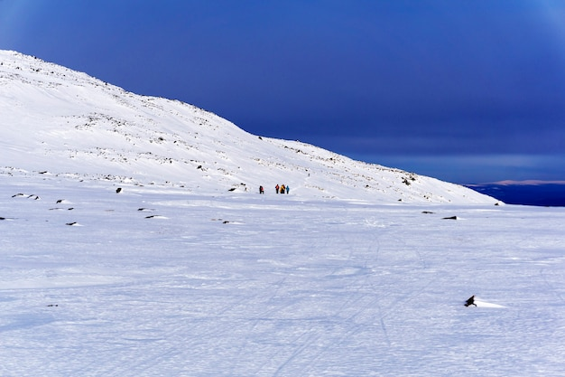 Groupe de touristes loin dans le paysage arctique montagneux sous un ciel bleu lumineux