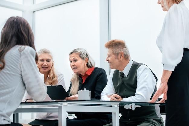 Le groupe de travail discute des tâches actuelles lors d'une réunion au bureau. concept d'entreprise