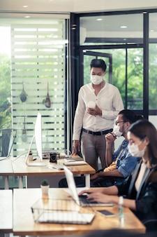 Un groupe de travail d'équipe interraciale porte un masque protecteur dans un nouveau bureau normal