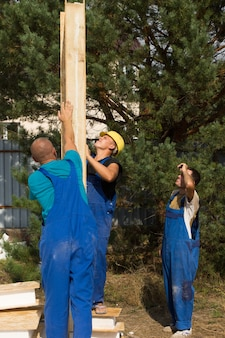 Groupe de travailleurs de la construction alignant un panneau mural en bois préfabriqué sur une nouvelle maison de construction
