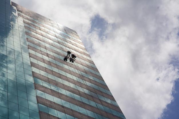 Groupe de travailleurs nettoyant le service de fenêtres sur un immeuble de grande hauteur