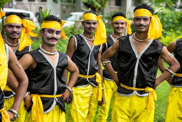 Groupe de tribus gondi célébrant la journée tribale mondiale en exécutant une danse folklorique