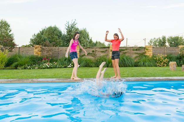 Groupe de trois amis adolescents s'amusant dans la piscine