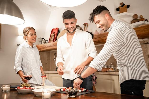 Groupe de trois amis à la maison préparer des collations salées pour l'apéritif - deux jeune homme et une jeune femme souriante dans la cuisine en attendant l'happy hour