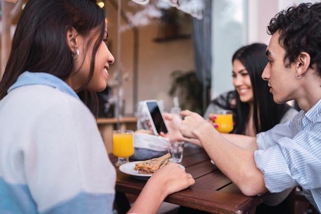 Groupe de trois étudiants latinos assis dans un café-bar regardant un smartphone.