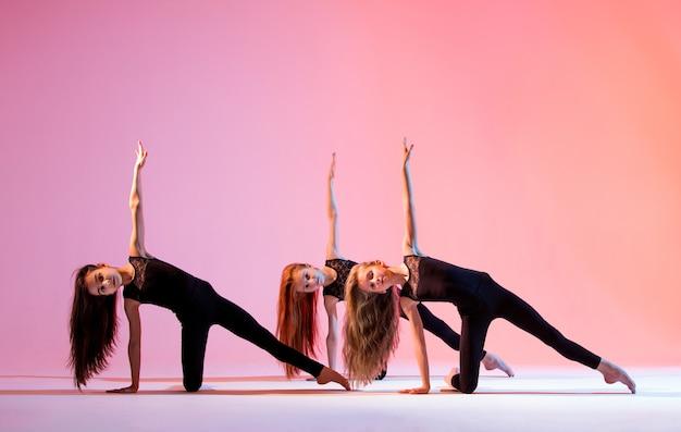 Un groupe de trois filles de ballet aux longs cheveux flottants en costumes noirs moulants dansent sur fond rouge