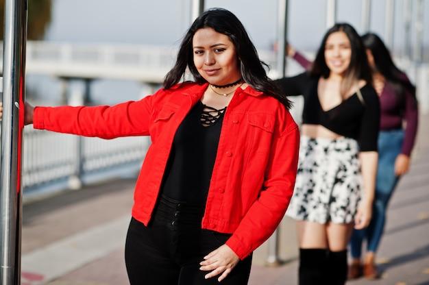 Groupe de trois filles latino-américaines heureuses et jolies d'equateur posées dans la rue