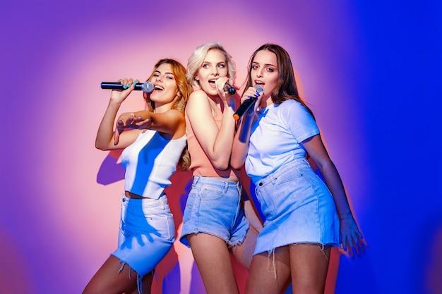 Groupe de trois jeunes filles souriantes chantant des chansons au microphone