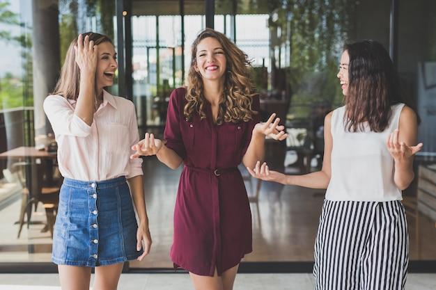 Groupe de trois meilleurs amis ayant une conversation en marchant ensemble