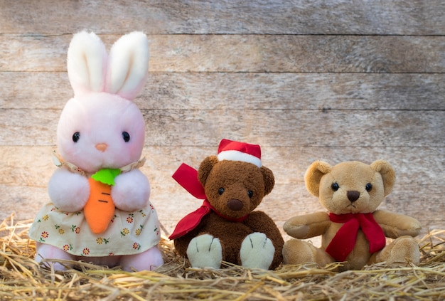 Groupe de trois poupées moelleuses mignonnes sur fond de paille et de bois