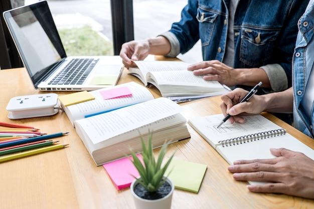 Groupe de tuteur ou d'étudiants collégiens assis à un bureau dans une bibliothèque étudiant et lisant, faisant ses devoirs