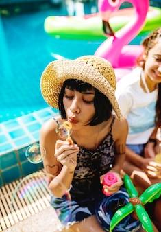 Un groupe varié d'amis appréciant l'été au bord de la piscine et jouant avec un barboteur de savon