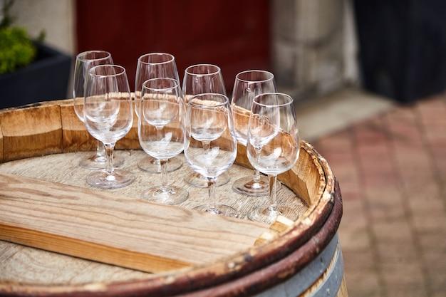 Groupe de verres à vin transparents vides debout sur un vieux tonneau en bois