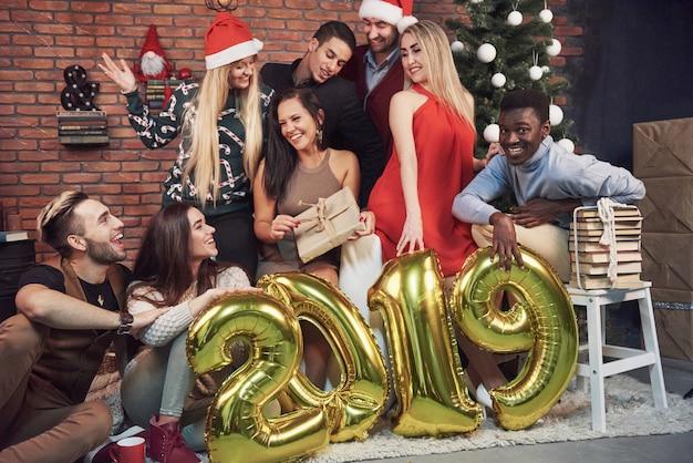 Un groupe de vieux amis joyeux a fait un cadeau à une fille. la nouvelle année 2019 arrive. célébrez le nouvel an dans une atmosphère chaleureuse