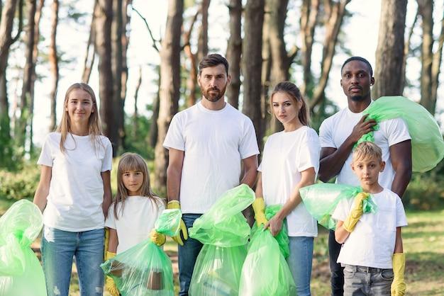 Groupe de volontaires internationaux multi-âges avec des sacs à ordures après le nettoyage de la zone.
