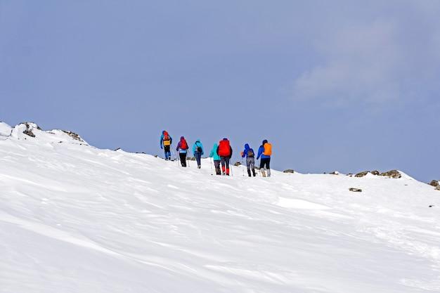 Groupe de voyageurs dans le paysage arctique montagneux sous un ciel bleu lumineux