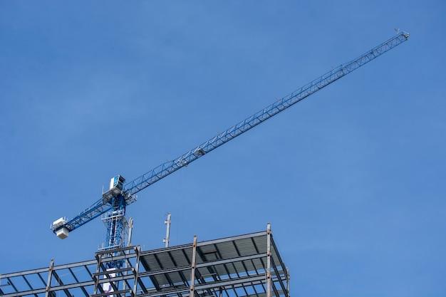 Grua de pluma en construccion con el cielo azul de fondo