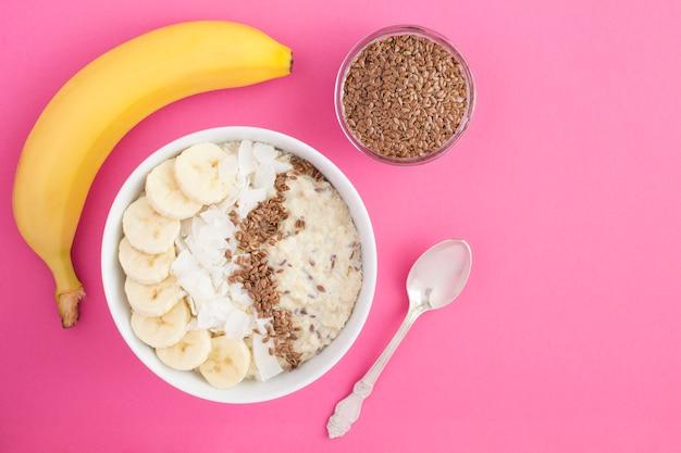 Gruau au lait avec graines de lin, banane et copeaux de noix de coco dans un bol blanc