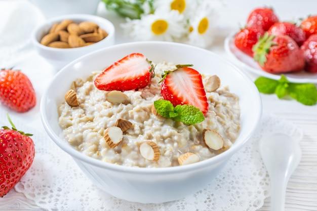 Gruau aux fraises et noix dans un bol sur la table en bois blanc.