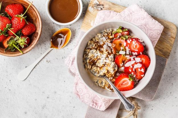 Gruau aux graines de chia, baies, graines et caramel dans un bol blanc