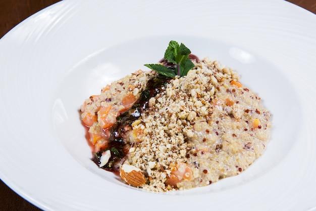 Gruau aux noix et sauce dans une assiette blanche sur une table en bois sombre dans un restaurant. savoureuse nourriture saine