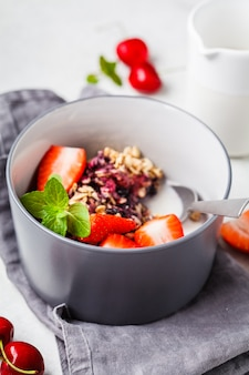Gruau cuit au four avec des baies et du lait dans un bol gris. petit déjeuner végétalien.