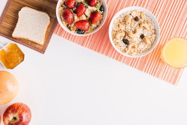 Gruau dans un bol avec du pain grillé et de la confiture sur une table blanche