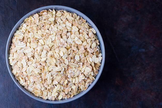 Gruau dans un bol. flocons d'avoine sur fond sombre. céréales pour faire un petit déjeuner sain. la nourriture végétarienne