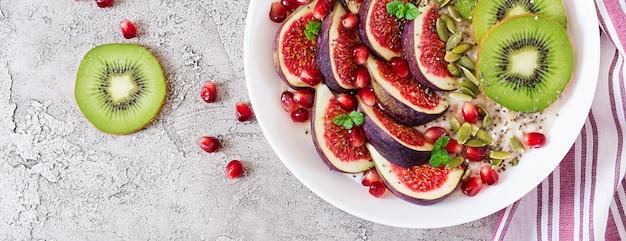 Gruau délicieux et sain avec des figues, du kiwi et de la grenade. petit-déjeuner sain. nutrition adéquat. mise à plat. vue de dessus.
