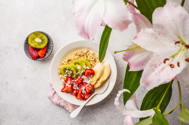 Gruau d'été avec fruits et noix de coco en plaque blanche.