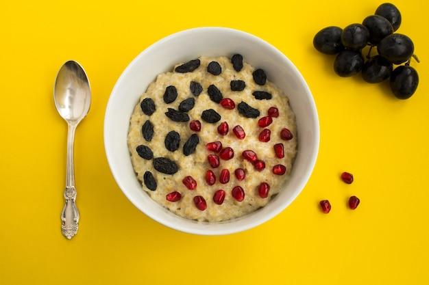 Gruau avec grenat et raisins secs dans la plaque blanche sur la surface jaune.vue d'en haut.