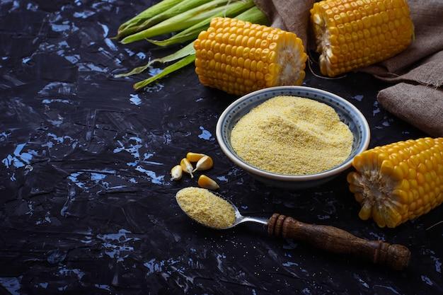 Gruau de maïs et épi de maïs sur fond de béton. mise au point sélective